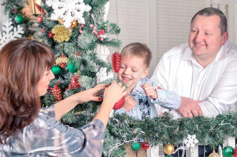 Famiglia che decora un albero di Natale con i boubles nel salone immagini stock