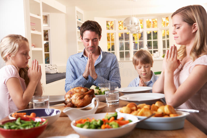 Famiglia che dice preghiera prima del cibo del pranzo dell'arrosto immagine stock libera da diritti