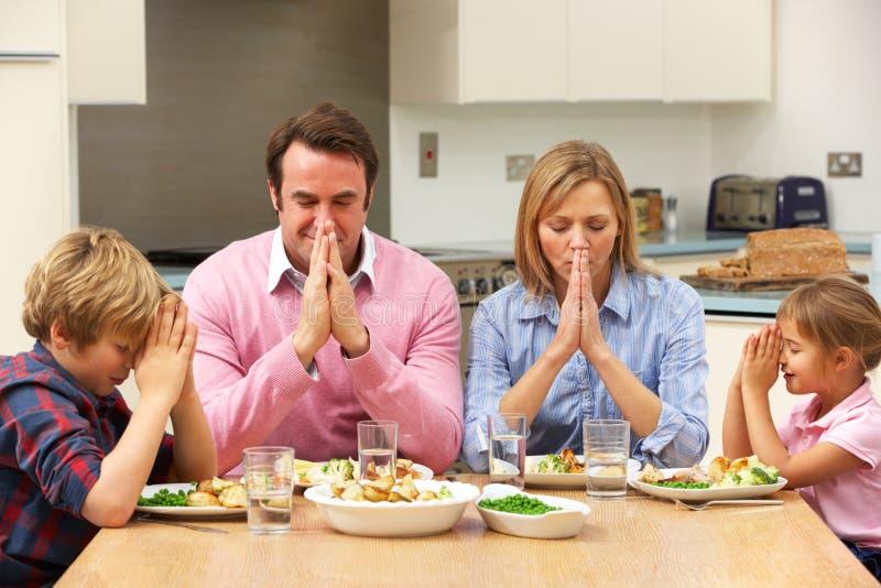 Famiglia che dice tolleranza prima del pasto fotografia stock