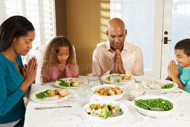 Famiglia che dice tolleranza prima del pasto a casa immagini stock libere da diritti