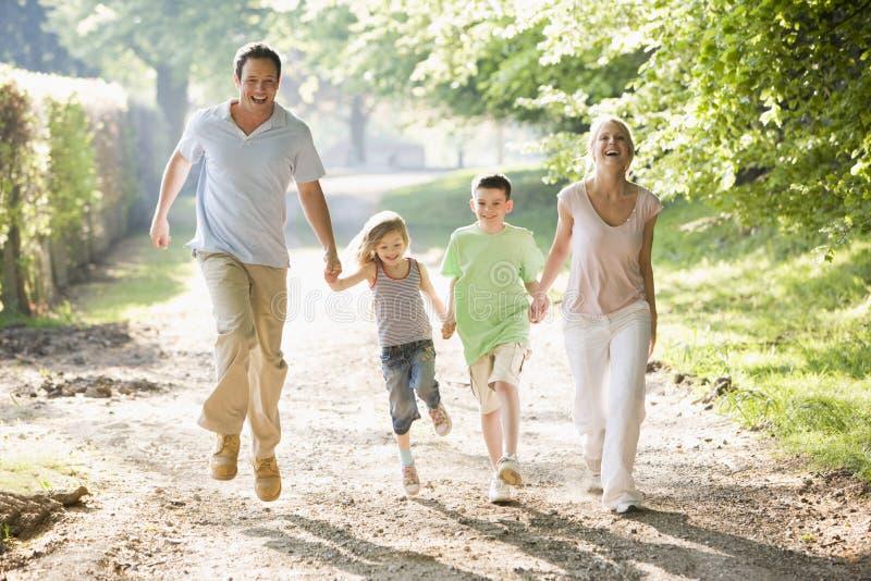 Famiglia che esegue all'aperto tenuta delle mani e sorridere fotografie stock libere da diritti