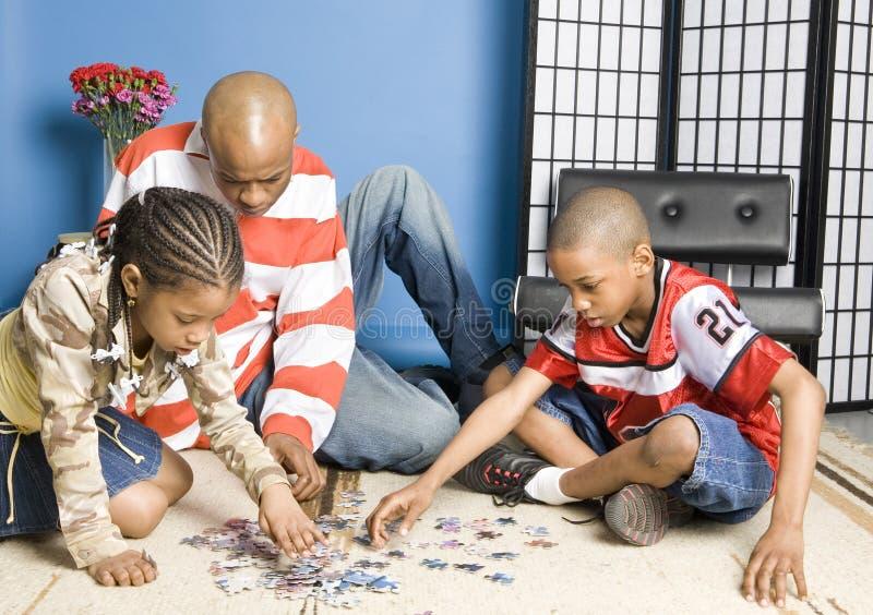 Famiglia che fa un puzzle fotografia stock libera da diritti