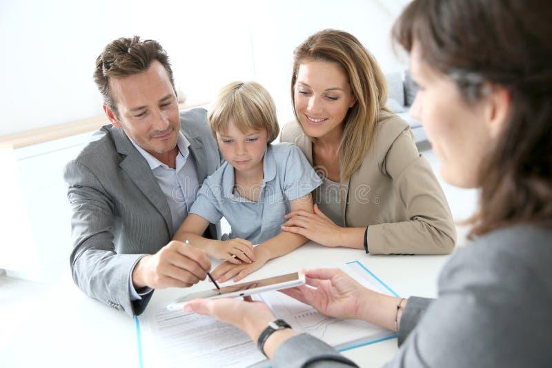 Famiglia che firma un contratto sulla compressa fotografia stock