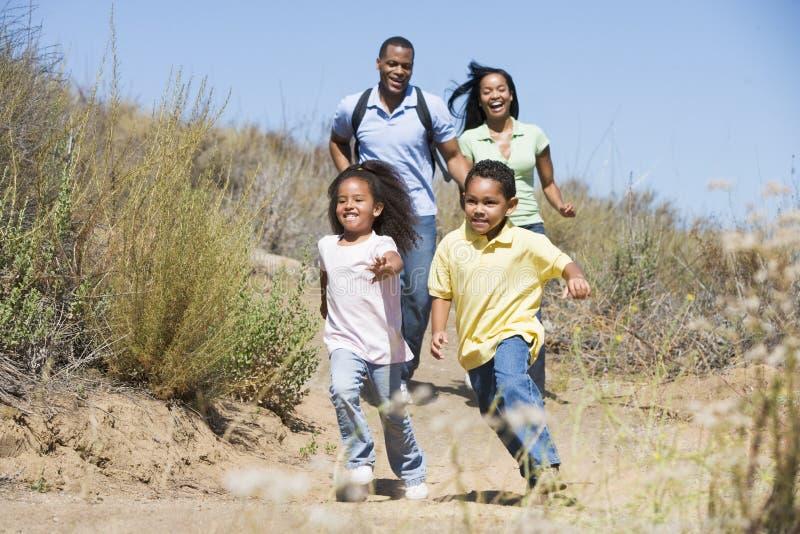 Famiglia che funziona sul sorridere del percorso immagine stock