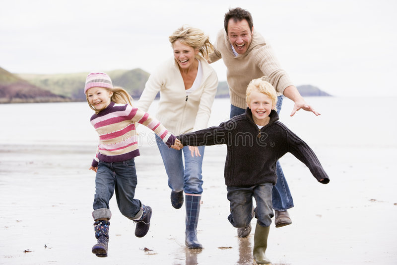 Famiglia che funziona sulle mani della holding della spiaggia immagini stock