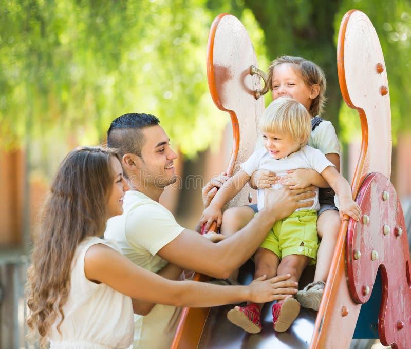 Famiglia che gioca allo scorrevole del ` s dei bambini fotografia stock libera da diritti