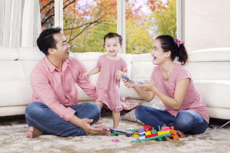 Famiglia che gioca con i giocattoli nel salone fotografia stock libera da diritti
