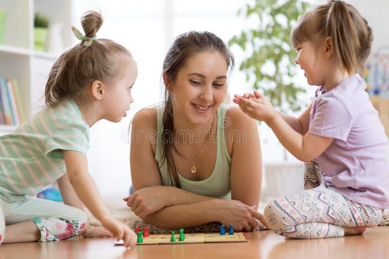 Famiglia che gioca gioco da tavolo Ludo a casa sul pavimento fotografia stock libera da diritti