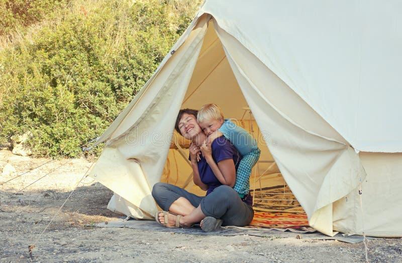 Famiglia che glamping vacanza all'aperto Madre ed suo figlio del bambino che si siedono vicino alla grande tenda di campeggio con immagine stock