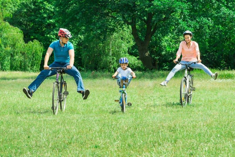 Famiglia che gode del giro sulla bicicletta al parco fotografia stock libera da diritti