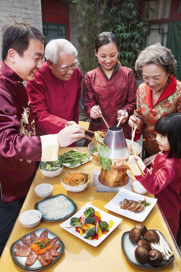 Famiglia che gode del pasto cinese in cinese l'abbigliamento del cinese tradizionale immagini stock libere da diritti
