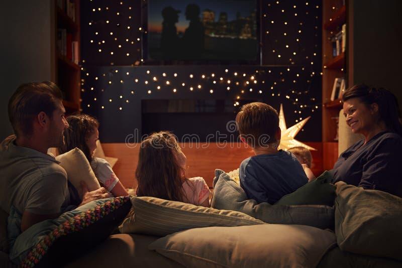 Famiglia che gode della notte di film a casa insieme fotografia stock libera da diritti
