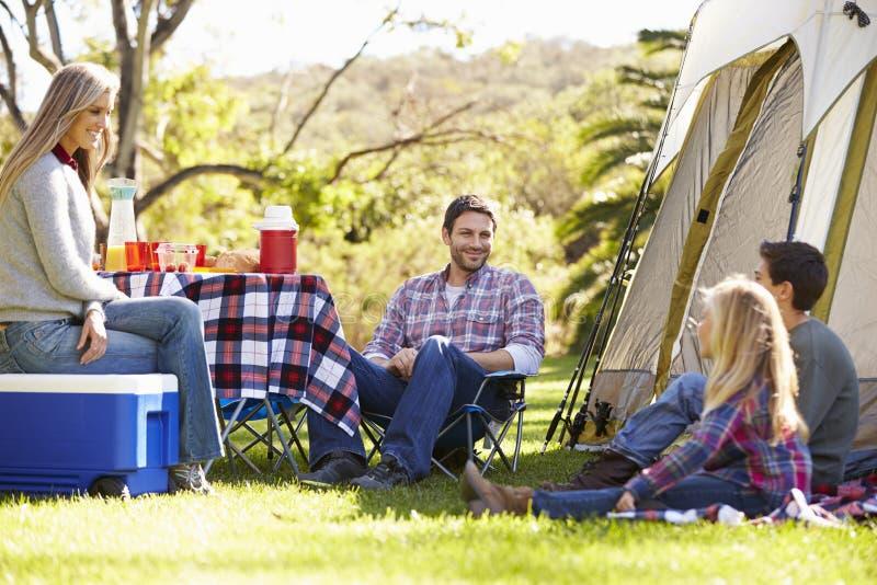 Famiglia che gode della vacanza in campeggio in campagna fotografia stock libera da diritti