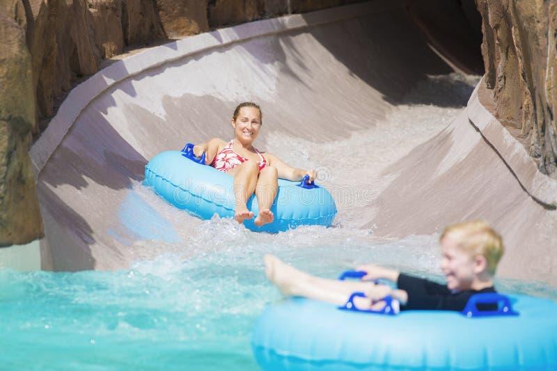 Famiglia che gode di un giro bagnato giù un acquascivolo fotografie stock libere da diritti
