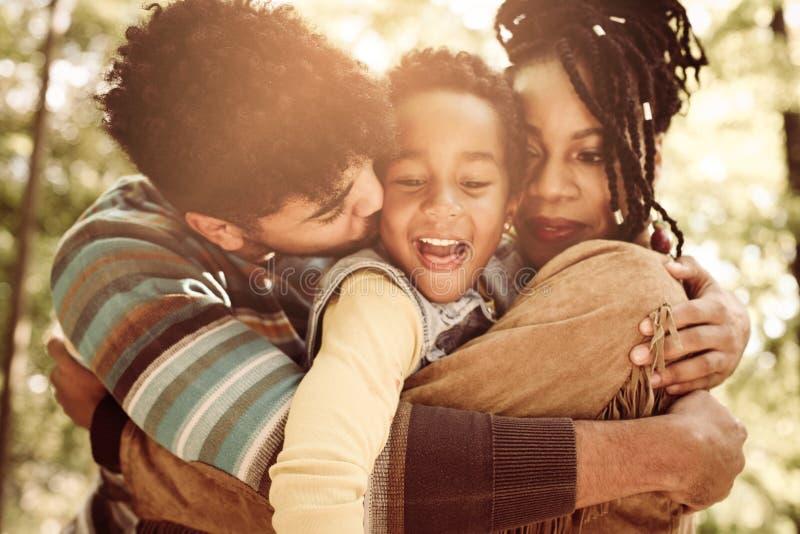 Famiglia che gode insieme nell'abbraccio in natura immagine stock libera da diritti