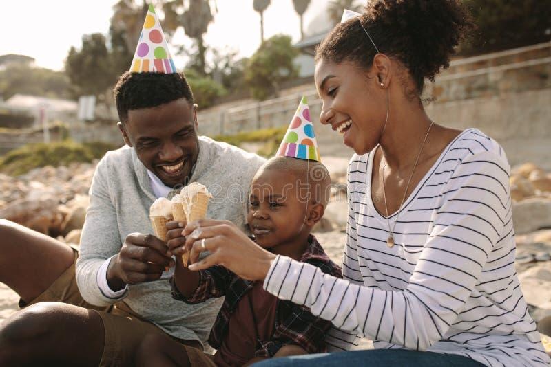 Famiglia che gode mangiando gelato sulla spiaggia fotografia stock libera da diritti
