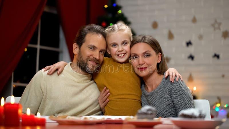 Famiglia che guarda alla macchina fotografica, albero di Natale che scintilla dietro, ritratto felice della gente immagine stock