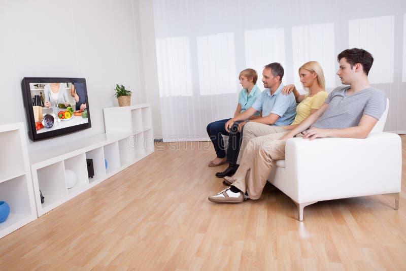Famiglia che guarda televisione a grande schermo fotografia stock