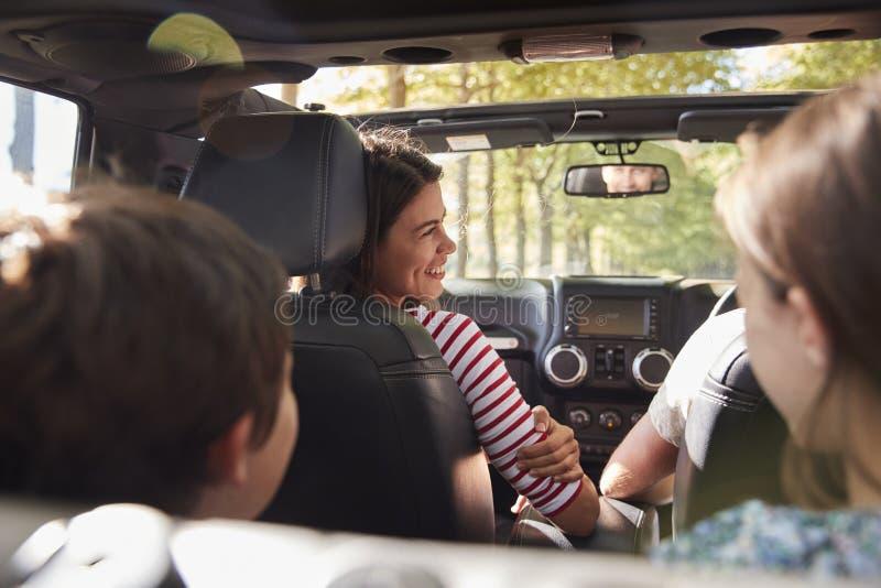 Famiglia che guida in automobile senza coperchio sul viaggio stradale della campagna fotografie stock libere da diritti