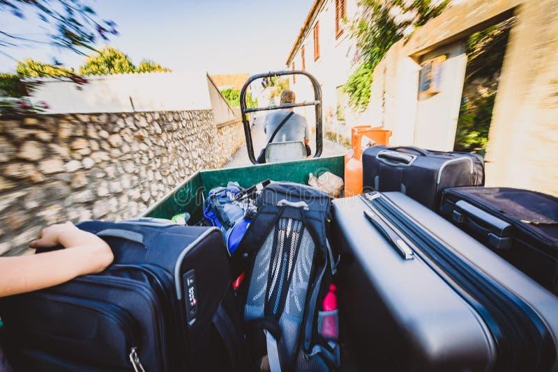 Famiglia che guida un rimorchio di trattore con le valigie ed i bagagli fotografie stock libere da diritti