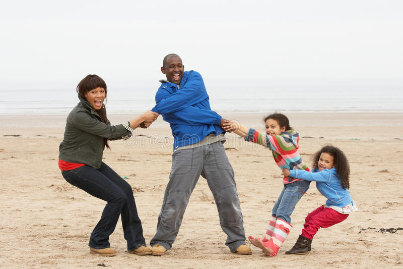 Famiglia che ha divertimento sulla spiaggia di inverno fotografia stock libera da diritti