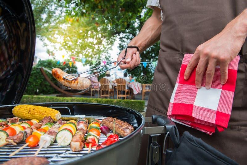 Famiglia che ha un partito del barbecue nel loro giardino immagini stock libere da diritti