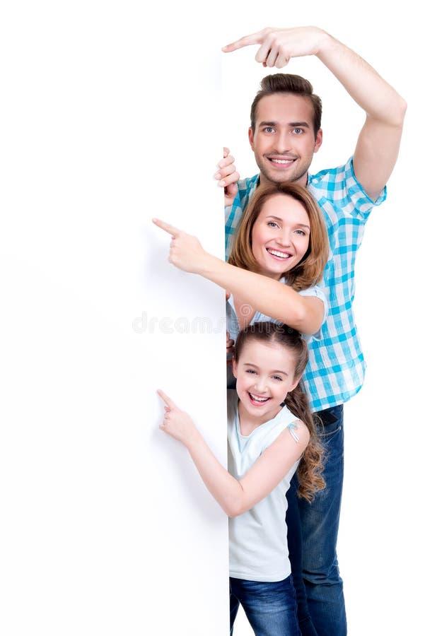 Famiglia che indica dal dito l'insegna immagine stock
