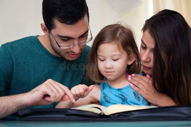 Famiglia che legge insieme la bibbia fotografia stock libera da diritti