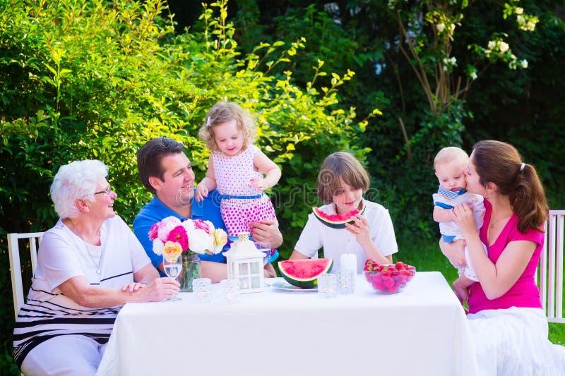 Famiglia che mangia frutta nel giardino immagine stock libera da diritti