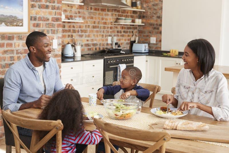 Famiglia che mangia insieme pasto nella cucina aperta di piano fotografie stock