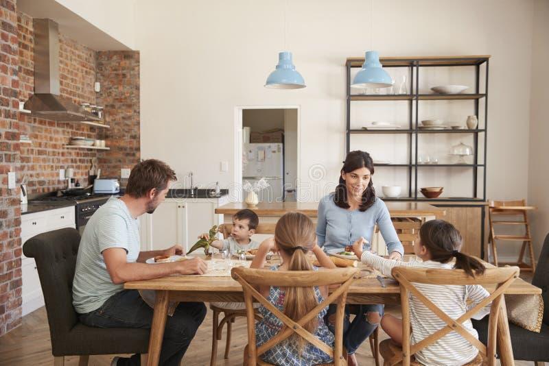 Famiglia che mangia insieme pasto nella cucina aperta di piano fotografie stock libere da diritti