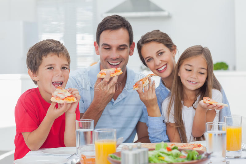 Famiglia che mangia le fette della pizza fotografia stock