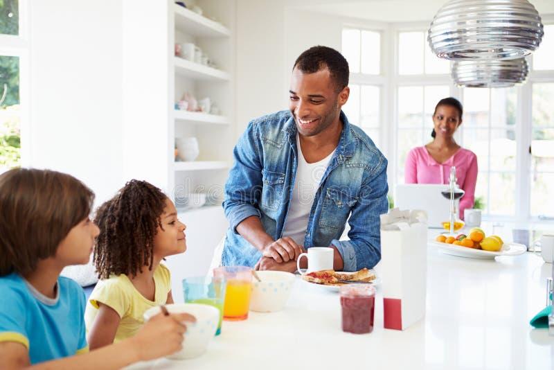 Famiglia che mangia prima colazione in cucina insieme fotografie stock