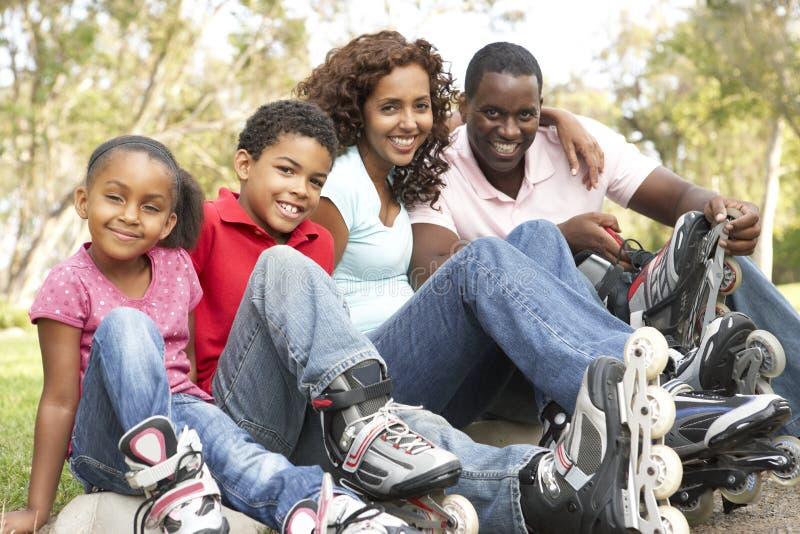 Famiglia che mette sopra nella riga pattini in sosta immagine stock