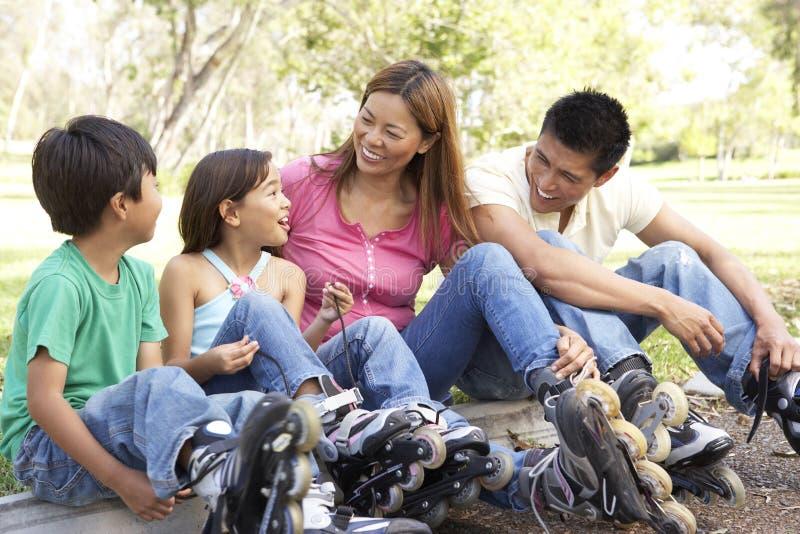 Famiglia che mette sopra nella riga pattini in sosta fotografia stock libera da diritti