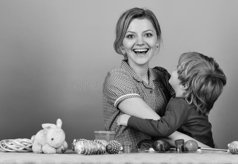 Famiglia che prepara per pasqua Donna, ragazzino con i sorrisi felici fotografie stock libere da diritti