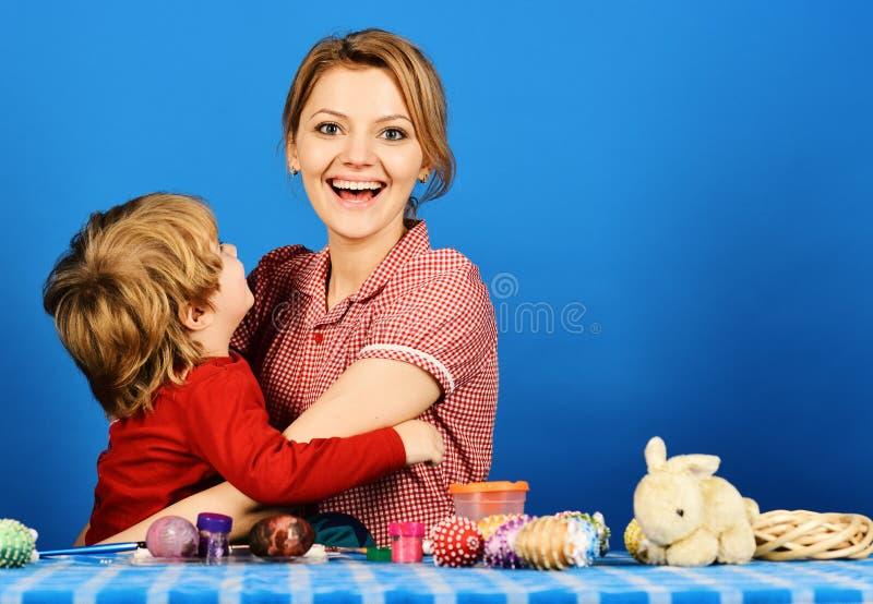 Famiglia che prepara per pasqua Donna, ragazzino con i sorrisi felici fotografia stock
