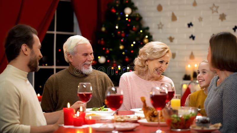 Famiglia che ride francamente durante la cena di Natale, le tradizioni e l'unità fotografia stock