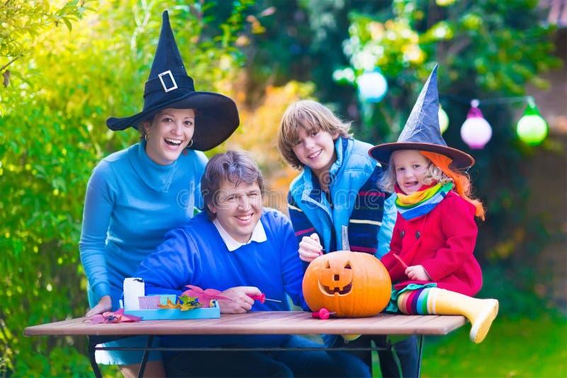 Famiglia che scolpisce zucca a Halloween fotografia stock libera da diritti