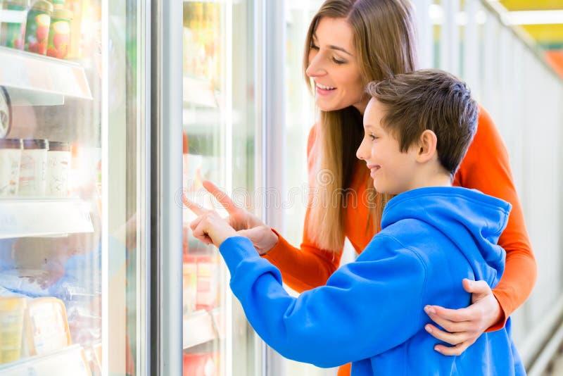 Famiglia che seleziona i prodotti raffreddati nell'ipermercato fotografia stock