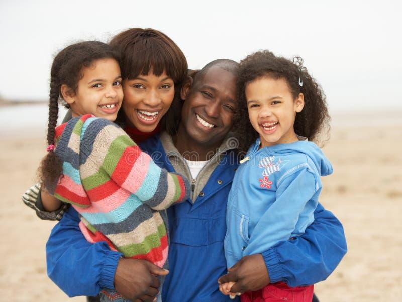 Famiglia che si distende sulla rottura della spiaggia di inverno fotografia stock libera da diritti