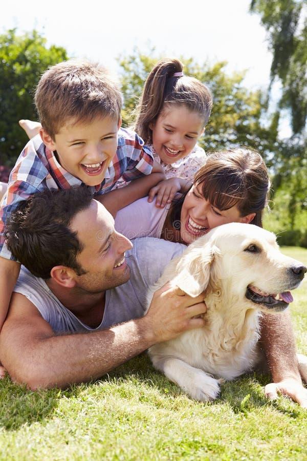 Famiglia che si rilassa nel giardino con il cane di animale domestico fotografie stock
