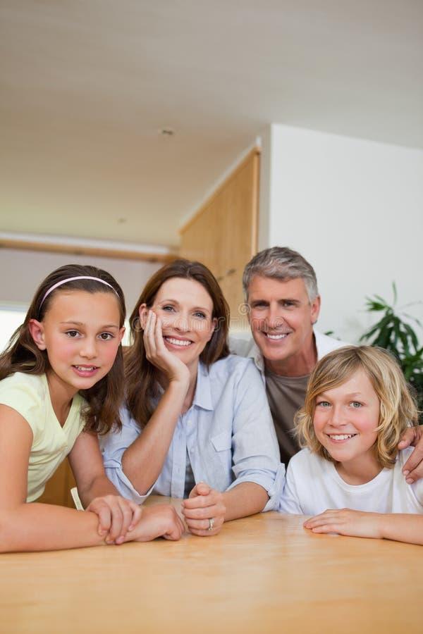 Famiglia che si siede alla tabella fotografia stock