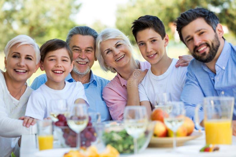 Famiglia che si siede alla tavola all'aperto, sorridendo immagine stock libera da diritti