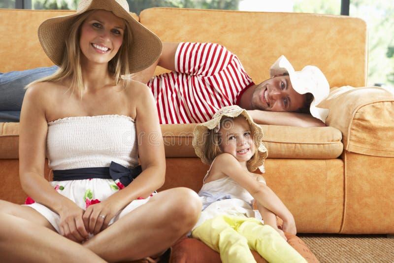 Famiglia che si siede in cappelli di Front Of Sofa Wearing Straw fotografie stock libere da diritti