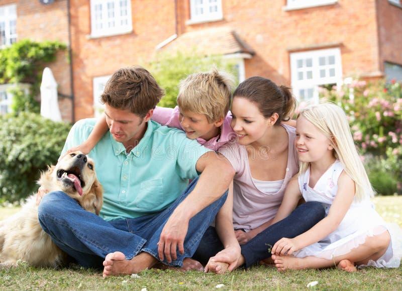 Famiglia che si siede insieme nel giardino fotografia stock