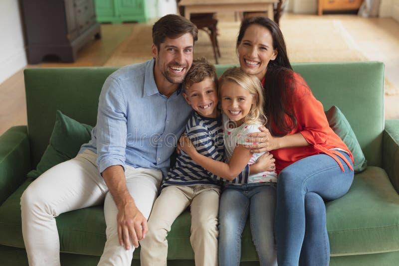 Famiglia che si siede insieme sul sofà nella casa di arte del salone immagine stock