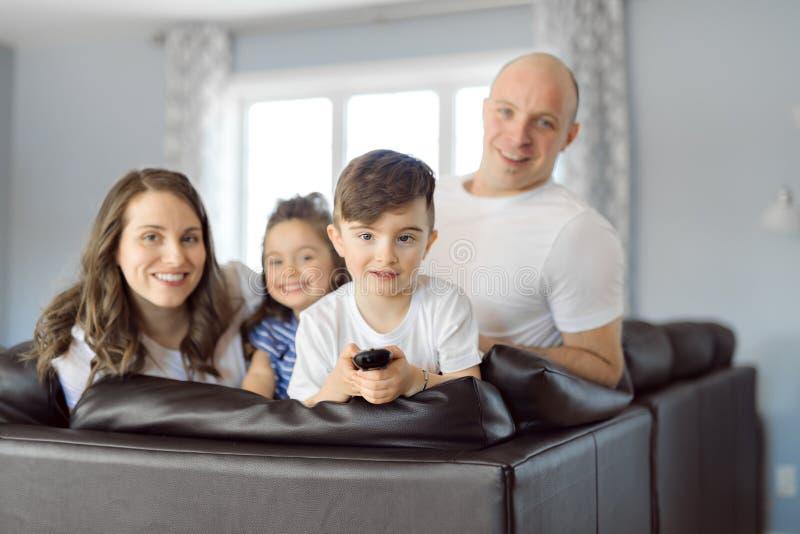 Famiglia che si siede nel salone con sorridere telecomandato immagine stock