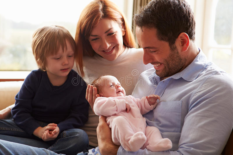 Famiglia che si siede su Sofa With Newborn Baby fotografia stock