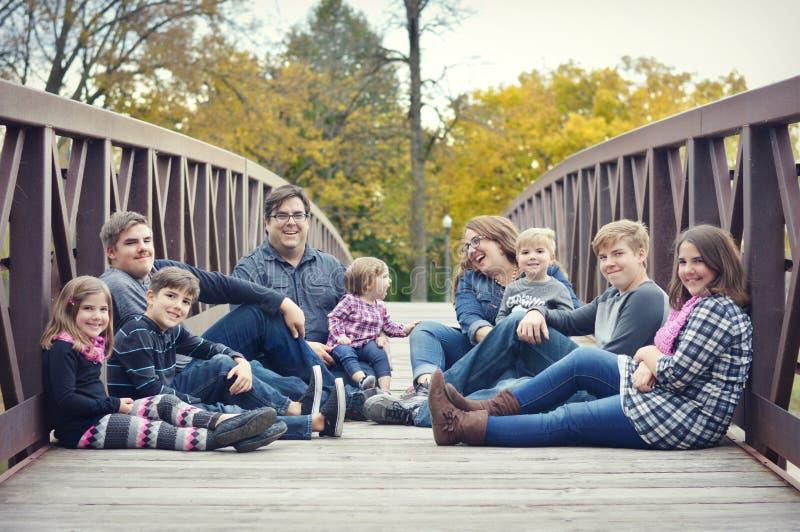 Famiglia che si siede su un ponte fotografia stock libera da diritti